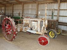 Antique tractors in an old barn Stock Photography