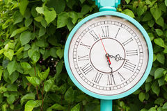 Antique turquoise color clock in the garden.  Royalty Free Stock Image