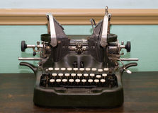 Antique Type Writer. An antique type writer sitting on a wooden table Royalty Free Stock Photo