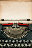 Antique typewriter with aged textured paper sheet. Space for your text Stock Photography