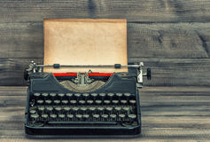 Antique typewriter with grungy textured paper page. Vintage style toned picture Royalty Free Stock Photography