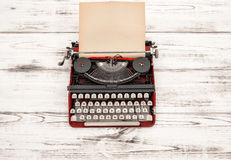 Antique typewriter with grungy textured paper page. On wooden table. Vintage style still life. German lettering Royalty Free Stock Images