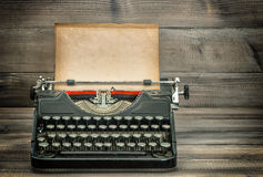 Antique typewriter with grungy worn paper page on wooden table Stock Photography