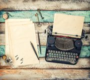 Antique typewriter used paper sheets Vintage toned. Antique typewriter and used paper sheets on wooden background. Vintage style toned picture stock images