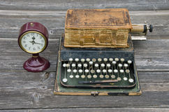 Antique typewriter, vintage clock and old book Bible. On wooden background. Memory concept Stock Photos