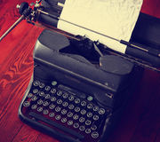 An antique typewriter on a wooden table toned with a retro vint Stock Images