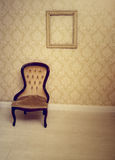 Antique upholstered chair in a wallpapered room. With an empty vintage wooden picture frame hanging on the wall suitable as an interior decorating background Royalty Free Stock Photography
