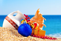 Antique vase, christmas baubles, gift box and seashell on the sa. Nd against blue ocean Stock Images