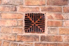 Antique ventilation brick grid. Ancient brick vent to allow air into a confined space. The wall the brick is centred in is hundreds of years old Royalty Free Stock Images