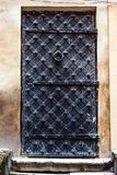 Antique vertical front door to the Middle Ages. Ancient aged closed vintage retro gothic grunge black iron metal door gate in old. City wall house building stock photos
