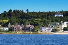 Antique village houses at Mackinac Island. View of Antique houses and village at Mackinac Island in beautiful Summer from lake. Here located at Straits Between Stock Photos