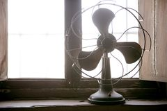 Antique vintage air fan. In the window backlight royalty free stock photo