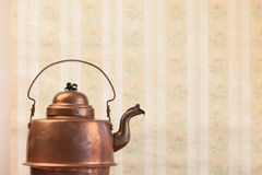 Antique vintage copper kettle on the background of old wallpaper Royalty Free Stock Images