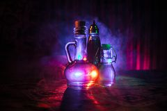 Antique and vintage glass bottle on dark foggy background with light. Poison or magic liquid concept. royalty free stock photo