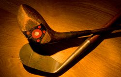 Antique, vintage golf clubs painted with light stock image