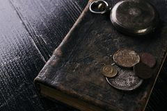 Antique vintage pocket watch and old leather book. With grunge coins on dark wooden table, close-up, top view. Time concept Royalty Free Stock Photos