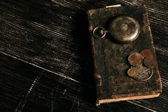 Antique vintage pocket watch and old leather book. With grunge coins on dark wooden table, close-up, top view. Time concept Stock Image