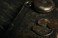 Antique vintage pocket watch and old leather book. With grunge coins on dark wooden table, close-up, top view. Time concept Royalty Free Stock Images