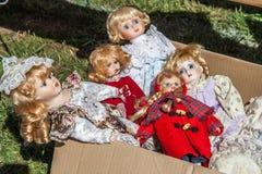 Antique and vintage porcelain or plastic dolls at flea market Stock Photography
