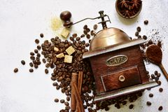 Antique vintage retro wooden coffee grinder on a light slate, st. Antique vintage retro wooden coffee grinder with ingredient for making drink on a light slate stock photos