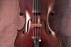 Antique violin against gray fabric background Royalty Free Stock Photo