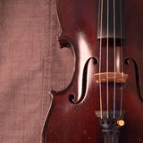 Antique violin against gray fabric background, square Stock Images