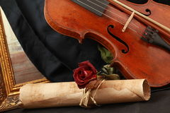 Antique violin, black silk and rose Stock Image