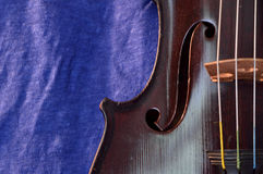 Antique violin and blue linen closeup Royalty Free Stock Images