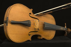 Antique violin with bow. The violin is a Stradivarius copy and the instrument with it's bow is isolated over a black background Royalty Free Stock Photography