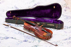 Antique Violin with Case. Hand made antique violin originally used by Hungarian Roma (gypsy). Resting on violin case with purple velvet lining. Bow alongside Royalty Free Stock Photo