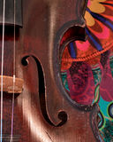 Antique violin closeup against bright print Royalty Free Stock Photo