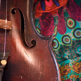 Antique violin closeup against colorful print Royalty Free Stock Images