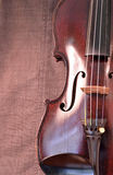 Antique violin closeup against gray fabric background vertical Stock Photos