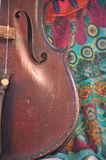 Antique violin closeup against quirky fabric print Stock Photography