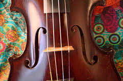 Antique violin closeup against vibrant print Stock Photo
