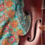 Antique violin closeup, square, against intricate pattern Royalty Free Stock Images