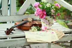 Antique violin, notes and spring bouquet Royalty Free Stock Image