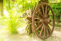 Wooden wheel on the grass. Antique wagon wheel at the courtyard farmhouse stock photos