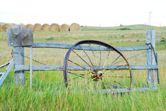 Antique wagon wheel leans against a fence in Montana. Stock Photos