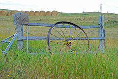 Antique wagon wheel leans against a fence in Montana. Royalty Free Stock Photography