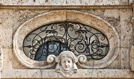 Antique wall architecural detail,marble head and grille Stock Image