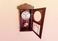 Antique wall clock with the front glass opened royalty free stock image