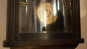 Antique wall clock with a pendulum closeup. stock footage