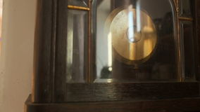 Antique wall clock with a pendulum closeup, slow mothion. stock video footage