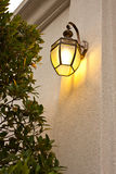 Antique wall lamp glowing orange in the evening Stock Photos