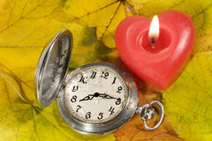 Antique watch and a candle on autumn leaves. Antique watch with raindrops on the face and red heart-shaped candle against the background of autumn leaves Royalty Free Stock Images