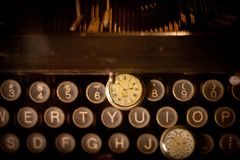 Antique watch on typewriter keys Royalty Free Stock Photo
