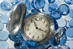 Antique watch under water. (with drops of water on the face) against the background of blue glass pebbles Stock Photo