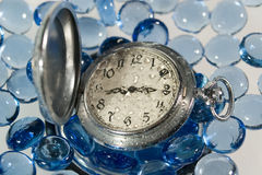 Antique watch under water. (with drops of water on the face) against the background of blue glass pebbles Stock Photos