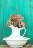 Antique water pitcher and basin with flowers by rustic green wood background Stock Photography